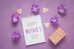 Μήνυμα ημέρας μητέρων με το κιβώτιο δώρων, τα πορφυρές λουλούδια και τις καρδιές επάνω Στοκ Εικόνες