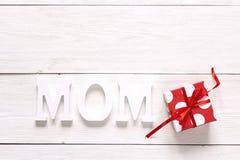 Μήνυμα ημέρας μητέρων με το κόκκινο κιβώτιο δώρων στο λευκό ξύλινο πίνακα Στοκ Εικόνες