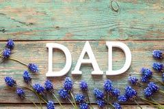 Μήνυμα ημέρας πατέρων με τα μπλε λουλούδια στο παλαιό ξύλινο υπόβαθρο στοκ εικόνες