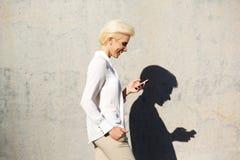 Μήνυμα κειμένου ανάγνωσης γυναικών χαμόγελου στο κινητό τηλέφωνο Στοκ Φωτογραφίες