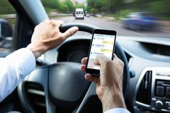 Μήνυμα κειμένου δακτυλογράφησης ατόμων στο κινητό τηλέφωνο Drive το αυτοκίνητο στοκ φωτογραφία με δικαίωμα ελεύθερης χρήσης