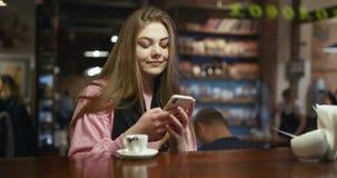 Μήνυμα κειμένου δακτυλογράφησης γυναικών στο έξυπνο τηλέφωνο σε έναν καφέ με έναν καφέ απόθεμα βίντεο