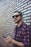 Μήνυμα κειμένου δακτυλογράφησης Πλάγια όψη του όμορφου νεαρού άνδρα στην έξυπνη περιστασιακή ένδυση που κρατά το κινητό τηλέφωνο  στοκ φωτογραφία με δικαίωμα ελεύθερης χρήσης