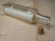 Μήνυμα στο ανοιγμένο μπουκάλι γυαλιού στο ξύλινο πάτωμα Στοκ Εικόνα