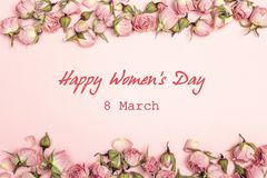 Μήνυμα χαιρετισμού ημέρας γυναικών ` s με τα μικρά ξηρά τριαντάφυλλα στο ρόδινο backgr στοκ εικόνες