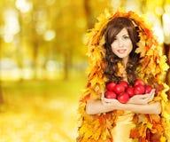 Μήλα εκμετάλλευσης γυναικών φθινοπώρου, πρότυπο μόδας στα κίτρινα φύλλα πτώσης Στοκ Εικόνα