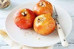 Μήλα με τα καρύδια σε ένα άσπρο πιάτο Στοκ Φωτογραφία