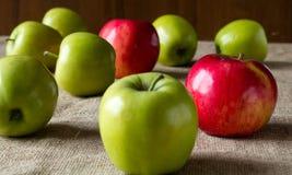 Μήλα που διασκορπίζονται στον πίνακα, καλυμμένο sackcloth Στοκ εικόνες με δικαίωμα ελεύθερης χρήσης