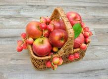 Μήλα σε ένα ψάθινο καλάθι σε ένα ξύλινο υπόβαθρο Στοκ εικόνα με δικαίωμα ελεύθερης χρήσης