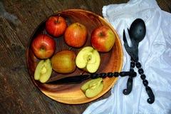 Μήλα στο ξύλινο πιάτο με το μαχαίρι σιδήρου Στοκ φωτογραφίες με δικαίωμα ελεύθερης χρήσης