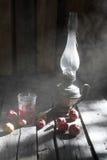 Μήλα, χυμός και ένας λαμπτήρας κηροζίνης στον πίνακα μέσα Στοκ Φωτογραφία