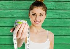 μήλο και μετρητής γυναικών ικανότητας με το πράσινο ξύλινο υπόβαθρο ελεύθερη απεικόνιση δικαιώματος