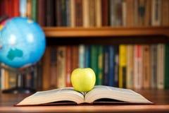 Μήλο στο βιβλίο Στοκ Φωτογραφίες