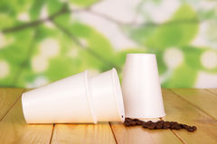 Μίας χρήσης φλυτζάνια εγγράφου και φασόλια καφέ στο αφηρημένο πράσινο υπόβαθρο Στοκ φωτογραφία με δικαίωμα ελεύθερης χρήσης