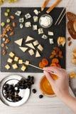 Μίγμα τυριών και φρούτων στη μαύρη πέτρα με το χέρι γυναικών Στοκ Φωτογραφία