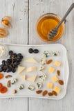 Μίγμα τυριών και φρούτων στο άσπρο κεραμικό πιάτο Στοκ εικόνες με δικαίωμα ελεύθερης χρήσης