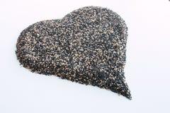 Μίγμα των γραπτών σπόρων σουσαμιού στη μορφή της καρδιάς στην άσπρη επιφάνεια Στοκ Φωτογραφία