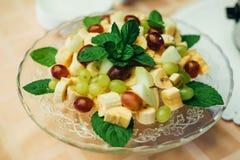 Μίγμα φρούτων στο πιάτο των μπανανών, των σταφυλιών και της Apple για την υγιεινή χορτοφάγο διατροφή Στοκ Εικόνες