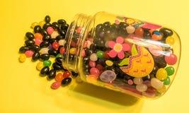 Μίγμα χρωματισμένων φασολιών ζελατίνας για τις διακοπές Πάσχας που ανατρέπουν από το πλαστικό εμπορευματοκιβώτιο καραμελών Πάσχας Στοκ φωτογραφία με δικαίωμα ελεύθερης χρήσης