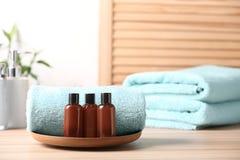 Μίνι μπουκάλια με τα καλλυντικά προϊόντα και πετσέτες στον πίνακα, διά στοκ εικόνες