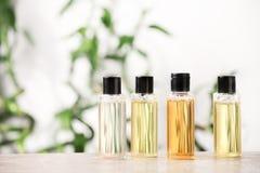 Μίνι μπουκάλια με τα καλλυντικά προϊόντα στον πίνακα στο θολωμένο κλί στοκ φωτογραφία με δικαίωμα ελεύθερης χρήσης