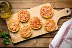 Μίνι πίτσα στον τέμνοντα πίνακα στοκ εικόνα με δικαίωμα ελεύθερης χρήσης