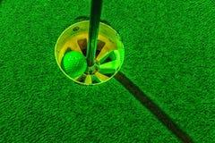 Μίνι σφαίρα γκολφ μέσα στην τρύπα στοκ εικόνες