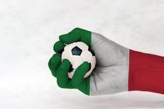 Μίνι σφαίρα του ποδοσφαίρου στο χρωματισμένο σημαία χέρι της Ιταλίας στο άσπρο υπόβαθρο Έννοια του αθλητισμού ή το παιχνίδι στη λ στοκ εικόνα με δικαίωμα ελεύθερης χρήσης