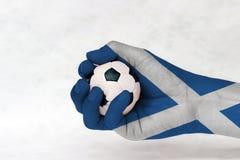 Μίνι σφαίρα του ποδοσφαίρου στο χρωματισμένο σημαία χέρι της Σκωτίας στο άσπρο υπόβαθρο Έννοια του αθλητισμού ή το παιχνίδι στη λ στοκ εικόνα