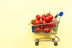 Μίνι σύνολο κάρρων παντοπωλείων αγορών των φρέσκων φρέσκων μούρων κερασιών στο κίτρινο υπόβαθρο Υγιής έννοια θερινών τροφίμων στοκ φωτογραφία με δικαίωμα ελεύθερης χρήσης