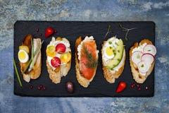 Μίνι σύνολο τροφίμων σάντουιτς Brushetta ή αυθεντικά παραδοσιακά ισπανικά tapas για τον πίνακα μεσημεριανού γεύματος Εύγευστο πρό Στοκ Εικόνα