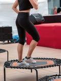 Μίνι τραμπολίνο Workout: Κορίτσι που κάνει την άσκηση ικανότητας στην κατηγορία στη γυμναστική στοκ φωτογραφία