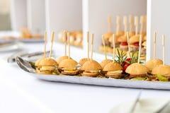 Μίνι χάμπουργκερ, τρόφιμα δάχτυλων, μίνι burgers, τρόφιμα κομμάτων, ολισθαίνοντες ρυθμιστές Στοκ εικόνα με δικαίωμα ελεύθερης χρήσης