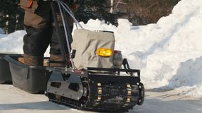 Μίνι όχημα για το χιόνι αντιολισθητικών αλυσίδων με ένα ρυμουλκό που πηγαίνει σε έναν χειμερινό δρόμο απόθεμα βίντεο