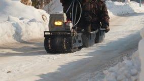 Μίνι όχημα για το χιόνι αντιολισθητικών αλυσίδων που πηγαίνει σε έναν χειμερινό δρόμο με ρυμουλκό και δύο επιβάτες απόθεμα βίντεο