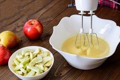 Μίξη του κτυπήματος ή της ζύμης για το κέικ Apple-αχλαδιών ή muffin ή την τηγανίτα Κλείστε επάνω στα ξύλινα επιτραπέζια γ συστατι Στοκ εικόνες με δικαίωμα ελεύθερης χρήσης