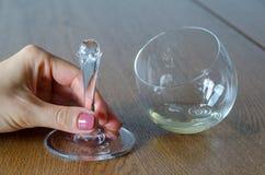 Μίσχος λαβής χεριών γυναικών ` s του σπασμένου γυαλιού κρασιού με το άσπρο κρασί στο W Στοκ εικόνα με δικαίωμα ελεύθερης χρήσης