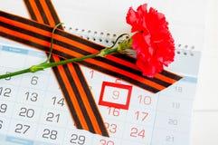9 Μαΐου εορταστικό υπόβαθρο με το κόκκινο γαρίφαλο και κορδέλλα του ST George στο ημερολόγιο με την ημερομηνία στις 9 Μαΐου Στοκ εικόνες με δικαίωμα ελεύθερης χρήσης