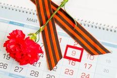 9 Μαΐου εορταστικό υπόβαθρο με το κόκκινο γαρίφαλο και κορδέλλα του ST George στο ημερολόγιο με την ημερομηνία στις 9 Μαΐου Στοκ Εικόνα