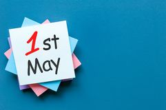 1 Μαΐου η ημέρα 1 μπορεί μήνας, ημερολόγιο στο σωρό των σημειώσεων στο μπλε υπόβαθρο με το διάστημα αντιγράφων για το πρότυπο ή π Στοκ Εικόνα
