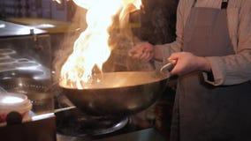Μαγείρεμα αρχιμαγείρων με την πυρκαγιά στο τηγάνισμα του τηγανιού φιλμ μικρού μήκους