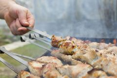 Μαγείρεμα ατόμων, μόνο χέρια, είναι τέμνουσα κρέας ή μπριζόλα για ένα πιάτο Εύγευστο ψημένο στη σχάρα κρέας στη σχάρα Σαββατοκύρι Στοκ φωτογραφίες με δικαίωμα ελεύθερης χρήσης