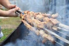 Μαγείρεμα ατόμων, μόνο χέρια, είναι τέμνουσα κρέας ή μπριζόλα για ένα πιάτο Εύγευστο ψημένο στη σχάρα κρέας στη σχάρα Σαββατοκύρι Στοκ Φωτογραφίες