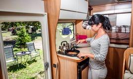 Μαγείρεμα γυναικών στο τροχόσπιτο, motorhome εσωτερικό Στοκ Εικόνες
