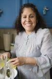 Μαγείρεμα γυναικών χαμόγελου μέσης ηλικίας στην κουζίνα στοκ φωτογραφία με δικαίωμα ελεύθερης χρήσης
