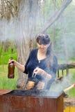 Μαγείρεμα γυναικών χαμόγελου υπαίθρια άνω BBQ Στοκ Εικόνες