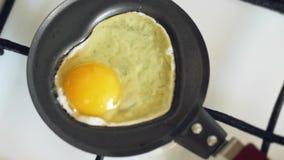 Μαγείρεμα ενός τηγανισμένου αυγού σε ένα μίνι τηγάνι με μορφή μιας καρδιάς φιλμ μικρού μήκους