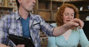 Μαγείρεμα ζεύγους στην κουζίνα που χρησιμοποιεί μαζί τη συνταγή από υπολογιστή, τον άνδρα και τη γυναίκα ταμπλετών τον ψηφιακό πο φιλμ μικρού μήκους