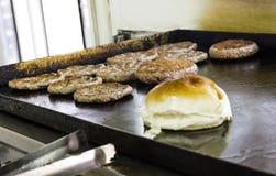Μαγείρεμα και ξέφτισμα Burgers και χάμπουργκερ στη σχάρα με τη φραντζόλα ψωμιού στοκ εικόνα