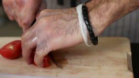 Μαγείρεμα και υπαίθρια έννοια - κλείστε επάνω της αρσενικής τέμνουσας ντομάτας χεριών στον τέμνοντα πίνακα με το αιχμηρό μαχαίρι φιλμ μικρού μήκους